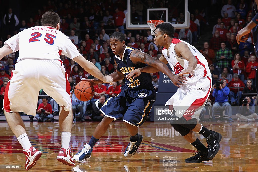 Isaiah Canaan #3 of the Murray State Racers handles the ball against pressure from Vee Sanford #43 and Alex Gavrilovic #25 of the Dayton Flyers during the game at University of Dayton Arena on December 22, 2012 in Dayton, Ohio. The Flyers won 77-68.