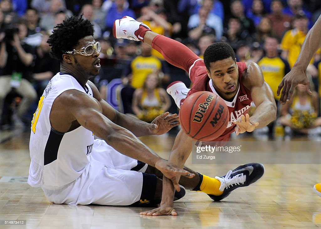 Isaiah Cousins of the Oklahoma Sooners looses the ball and is charged with traveling against Devin Williams of the West Virginia Mountaineers in the...