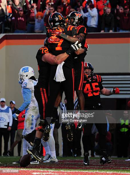 Isaiah Ford of the Virginia Tech Hokies is congratulated by Bucky Hodges after making a catch for a touchdown against the North Carolina Tar Heels on...