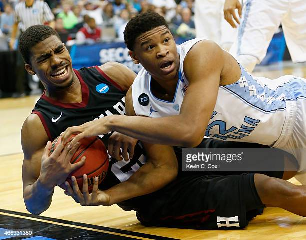 Isaiah Hicks of the North Carolina Tar Heels and Wesley Saunders of the Harvard Crimson battle for a loose ball during the second round of the 2015...