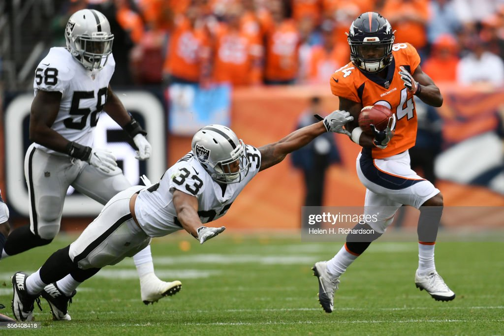 Isaiah McKenzie (84) of the Denver Broncos runs away from DeAndre Washington (33) of the Oakland Raiders and Tyrell Adams (58) as he returns a punt from Marquette King (7) during the third quarter on Sunday, October 1, 2017. The Denver Broncos hosted the Oakland Raiders.