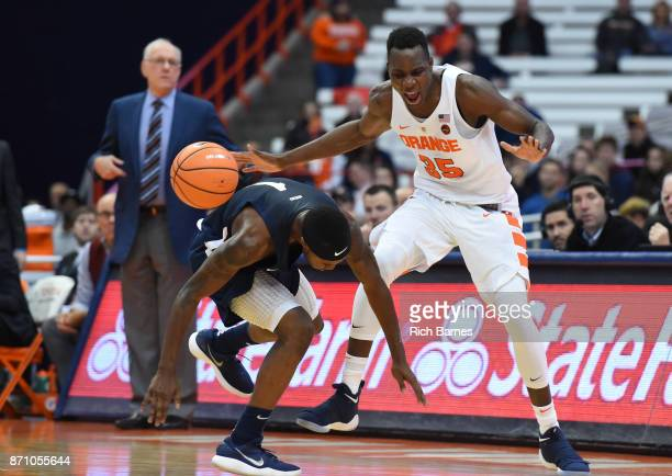 Isaiah McLeod of the Southern Connecticut State Owls and Bourama Sidibe of the Syracuse Orange reacts to a loose ball during the first half at the...