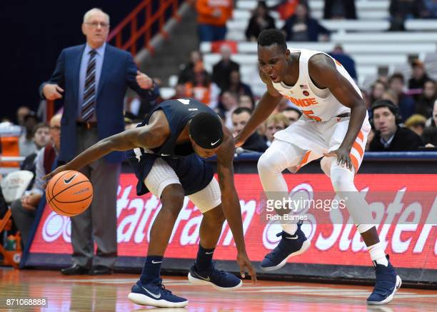 Isaiah McLeod of the Southern Connecticut State Owls and Bourama Sidibe of the Syracuse Orange react to a loose ball during the first half at the...