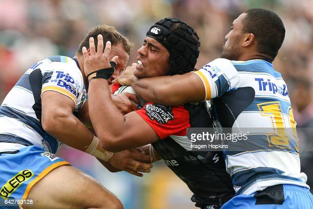 Isaiah Papalii of the Warriors is tackled by Tyrone Roberts and Lorenzo Ma'afu of the Titans during the NRL Trial match between the Warriors and the...