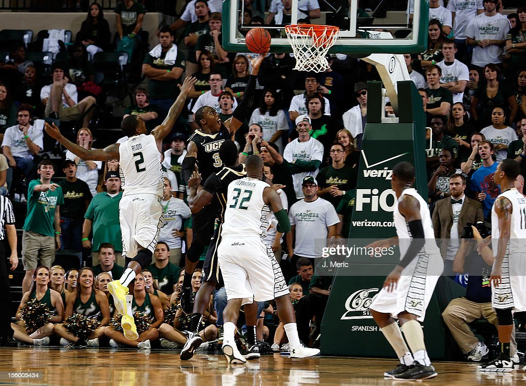 Isaiah Sykes #3 of the Central Florida Knights drives to the basket as Victor Rudd #2 and Toarlyn Fitzpatrick #32 of the South Florida Bulls defend during the game at the Sun Dome on November 10, 2012 in Tampa, Florida.