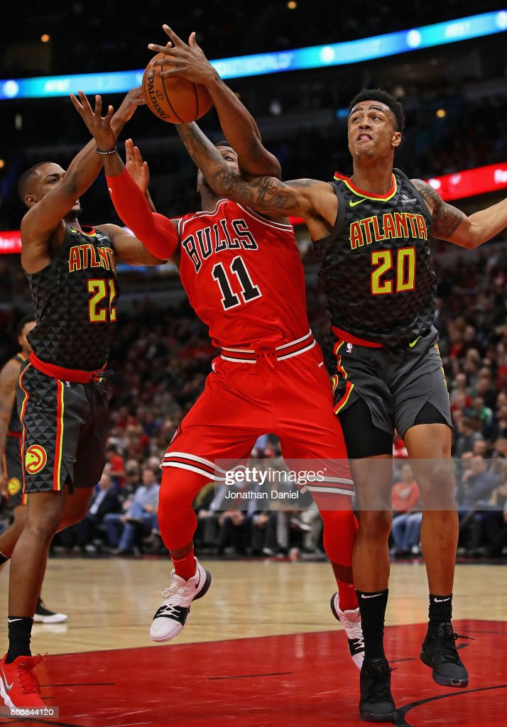 Isaiah Taylor #22 and John Collins #20 of the Atlanta Hawks knock the ball away from David Nwaba #11 of the Chicago Bulls at the United Center on October 26, 2017 in Chicago, Illinois.