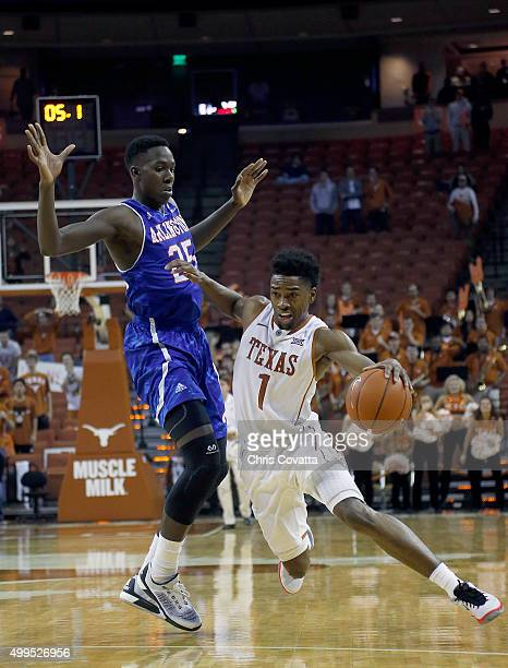 Isaiah Taylor of the Texas Longhorns drives around Kevin Hervey of the TexasArlington Mavericks at the Frank Erwin Center on December 1 2015 in...