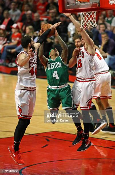 Isaiah Thomas of the Boston Celtics puts up a shot between Nikola Mirotic and Paul Zipser of the Chicago Bulls during Game Four of the Eastern...