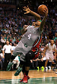 Isaiah Thomas of the Boston Celtics shoots as he falls to the ground against Hassan Whiteside of the Miami Heat in the fourth quarter at TD Garden on...