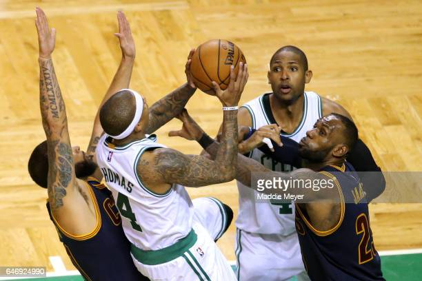 Isaiah Thomas of the Boston Celtics takes a shot against Deron Williams of the Cleveland Cavaliers and LeBron James during the fourth quarter at TD...