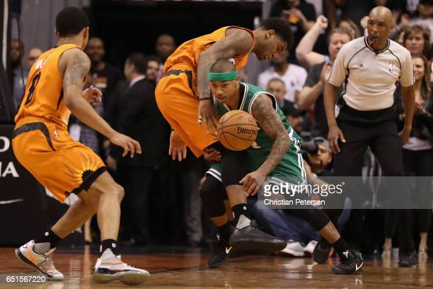 Isaiah Thomas of the Boston Celtics turns over the ball to Marquese Chriss and Tyler Ulis of the Phoenix Suns during the second half of the NBA game...