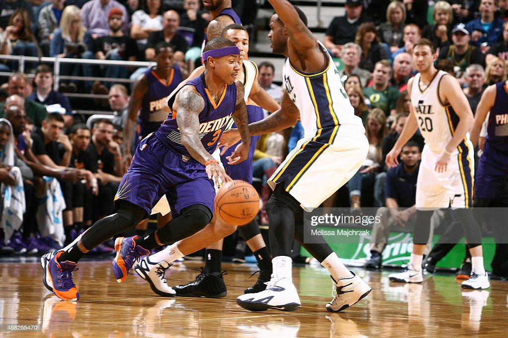 Isaiah Thomas of the Phoenix Suns drives around Trevor Booker of the Utah Jazz at EnergySolutions Arena on November 01 2014 in Salt Lake City Utah...