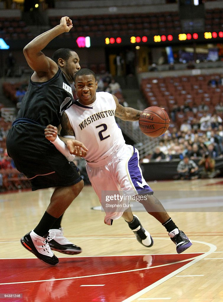 Isaiah Thomas of the Washington Huskies drives around Austin Freeman of the Georgetown Hoyas in the John Wooden Classic on December 12 2009 at the...