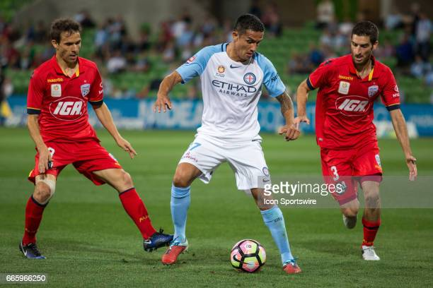 Isaias of Adelaide United and Iacopo La Rocca of Adelaide United attempt to tackle Tim Cahill of Melbourne City who is controlling the ball during...