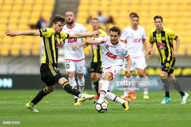 Isaias of Adelaide United passes under pressure from Alex Rufer of the Phoenix during the round one ALeague match between Wellington Phoenix and...