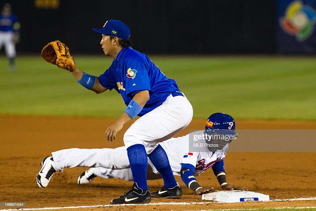 Isaias Velasquez #7 of Team Panama slides back into first base as Daniel Matsumoto #31 of Team Brazil waits for the throw during Game 6 of the Qualifying Round of the World Baseball Classic between Team Panama and Team Brazil at Rod Carew National Stadium on Monday, November 19, 2012 in Panama City, Panama.