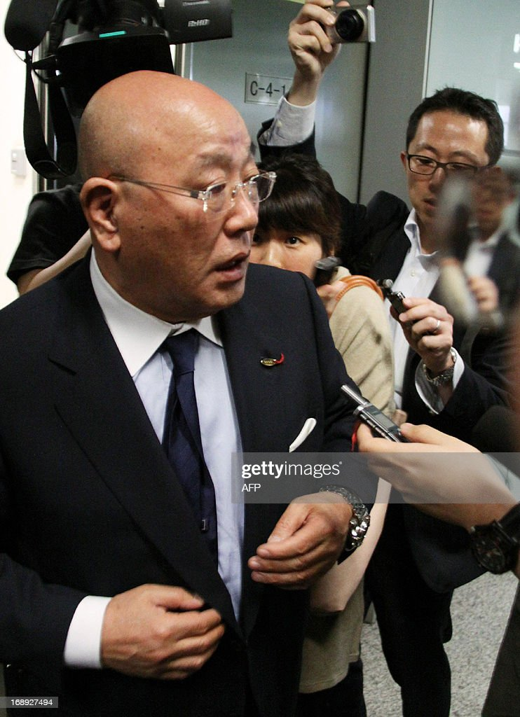 Isao Iijima, an adviser to Japanese Prime Minister Shinzo Abe, is surrounded by reporters upon his arrival at Beijing airport from Pyongyang on May 17, 2013. Iijima said he had held 'sincere' talks with North Korean officials during his controversial visit to the country, after a four-day visit to Pyongyang. AFP PHOTO / JIJI PRESS JAPAN OUT