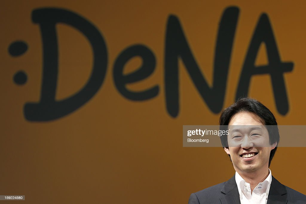 Isao Moriyasu, president of DeNA Co., smiles in front of the company's new logo as he attends a news conference in Tokyo, Japan, on Thursday, Jan. 10, 2013. DeNA will offer music services for iOS and Android platforms within this fiscal year, according to a statement today. Photographer: Kiyoshi Ota/Bloomberg via Getty Images