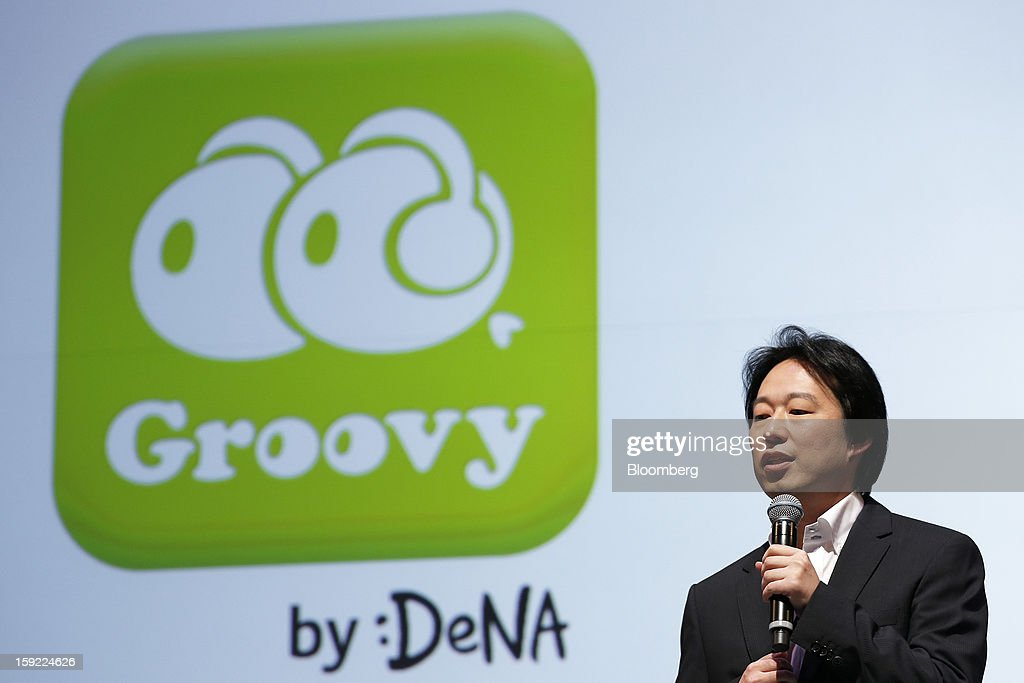 Isao Moriyasu, president of DeNA Co., speaks in front of the logo for Groovy, the company's social music app, during a news conference in Tokyo, Japan, on Thursday, Jan. 10, 2013. DeNA will offer music services for iOS and Android platforms within this fiscal year, according to a statement today. Photographer: Kiyoshi Ota/Bloomberg via Getty Images