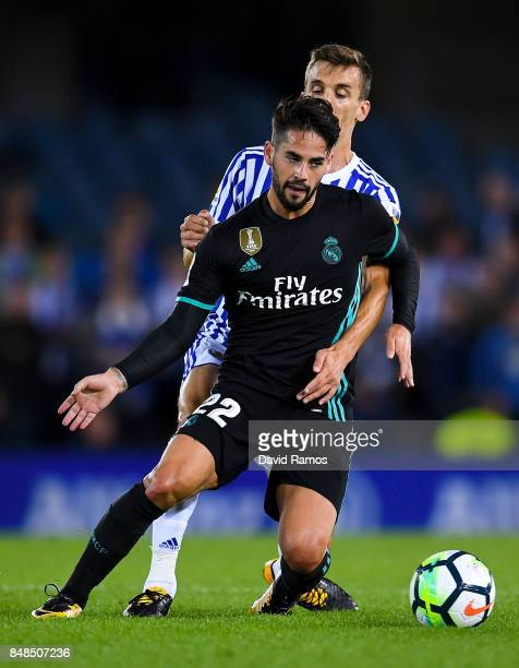 Isco Alarcon of Real Madrid CF competes for the ball with Diego Llorente of Real Sociedad de Futbol during the La Liga match between Real Sociedad...