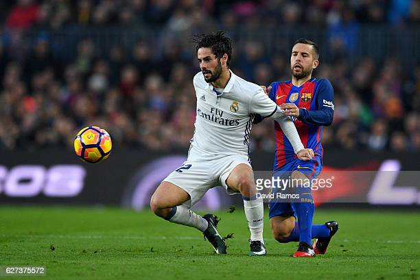 Isco of Real Madrid and Jordi Alba of Barcelona compete for the ball during the La Liga match between FC Barcelona and Real Madrid CF at Camp Nou on...
