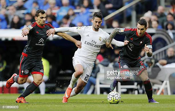 Isco of Real Madrid competes for the ball with Carles Planas and Jonny Castro of Celta Vigo during the La Liga match between Real Madrid CF and Celta...