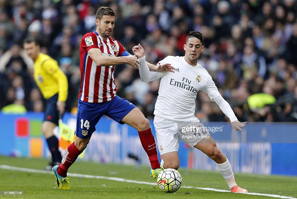 Isco of Real Madrid competes for the ball with Gabi of Club Atletico de Madrid during the La Liga match between Real Madrid CF and Club Atletico de Madrid at Estadio Santiago Bernabeu on February 27, 2016 in Madrid, Spain.