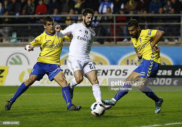 Isco of Real Madrid competes for the ball with Jon Ander Garrido and Cristian Marquez of Cadiz during the Copa del Rey round of 32 first leg match...