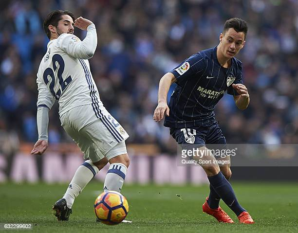 Isco of Real Madrid competes for the ball with Juan Pablo Anor of Malaga during the La Liga match between Real Madrid CF and Malaga CF at Estadio...