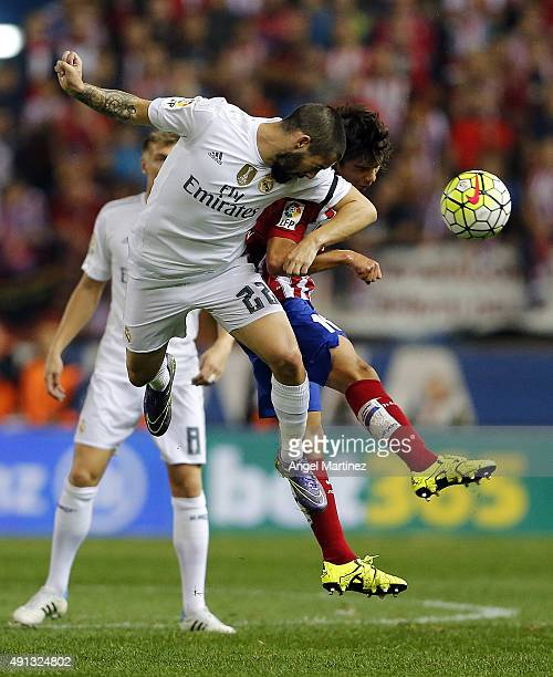 Isco of Real Madrid competes for the ball with Oliver Torres of Atletico de Madrid during the La Liga match between Club Atletico de Madrid and Real...