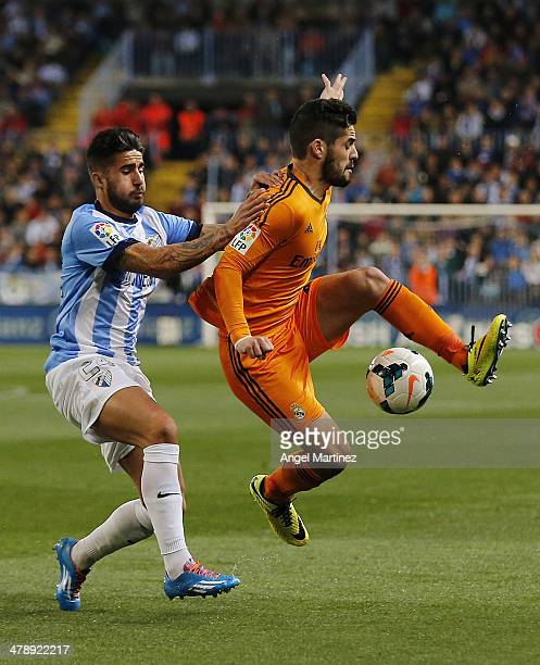 Isco of Real Madrid competes for the ball with Samuel Garcia of Malaga during the La Liga match between Malaga and Real Madrid at La Rosaleda Stadium...