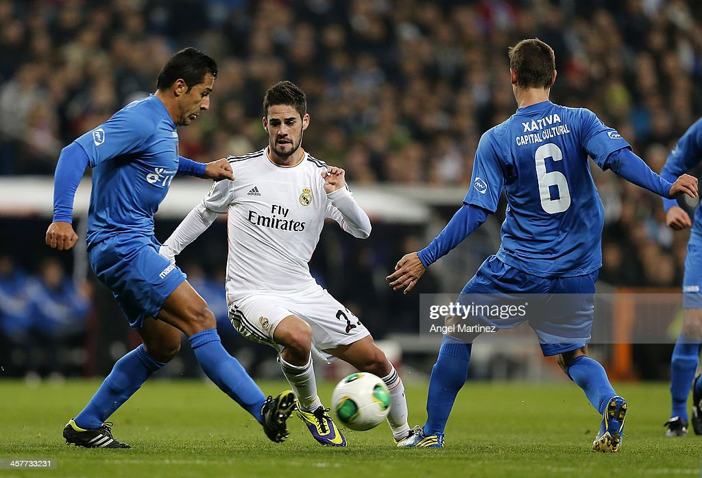 <a gi-track='captionPersonalityLinkClicked' href=/galleries/search?phrase=Isco&family=editorial&specificpeople=5848609 ng-click='$event.stopPropagation()'>Isco</a> of Real Madrid competes for the ball with Samuel Martinez (R) and Vicente Mendoza of Olimpic de Xativa during the Copa del Rey, round of 32 match between Real Madrid and Olimpic de Xativa at Estadio Santiago Bernabeu on December 18, 2013 in Madrid, Spain.