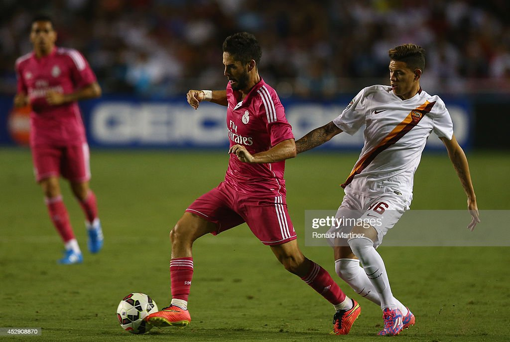 Isco #23 of Real Madrid dribbles the ball past Antonio Sanabria #96 of AS Roma during a Guinness International Champions Cup 2014 game at Cotton Bowl on July 29, 2014 in Dallas, Texas.
