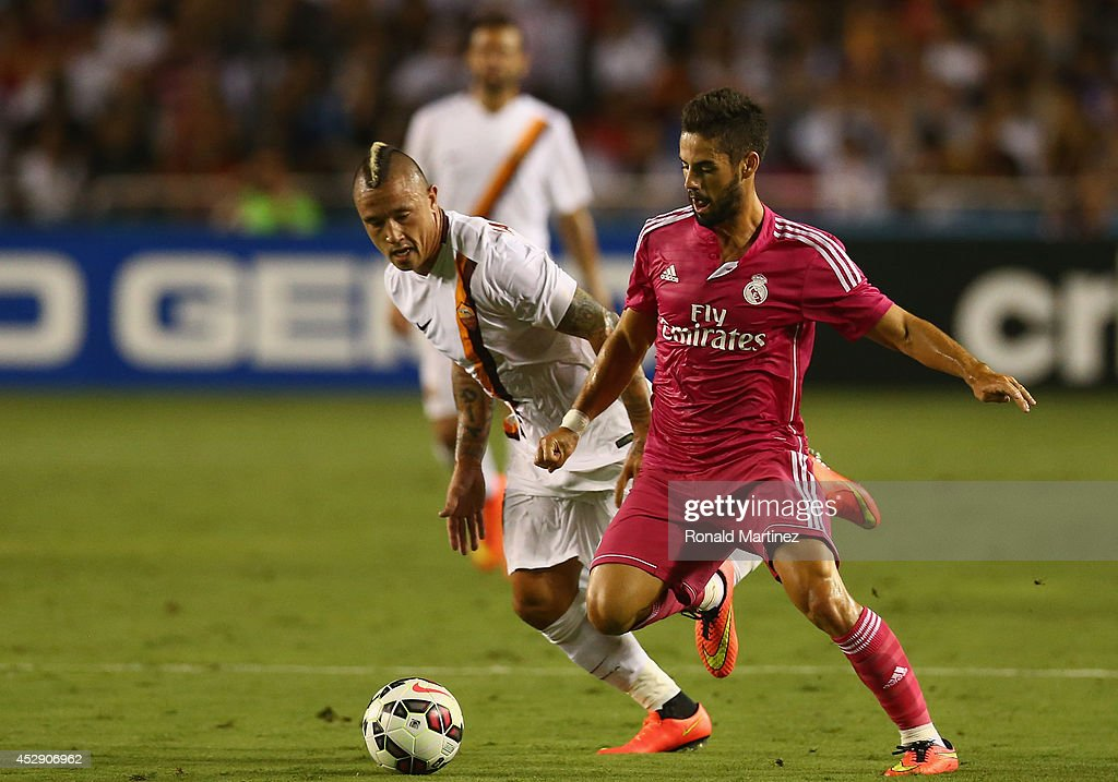 Isco #23 of Real Madrid dribbles the ball past Radja Nainggolan #4 of AS Roma during a Guinness International Champions Cup 2014 game at Cotton Bowl on July 29, 2014 in Dallas, Texas.
