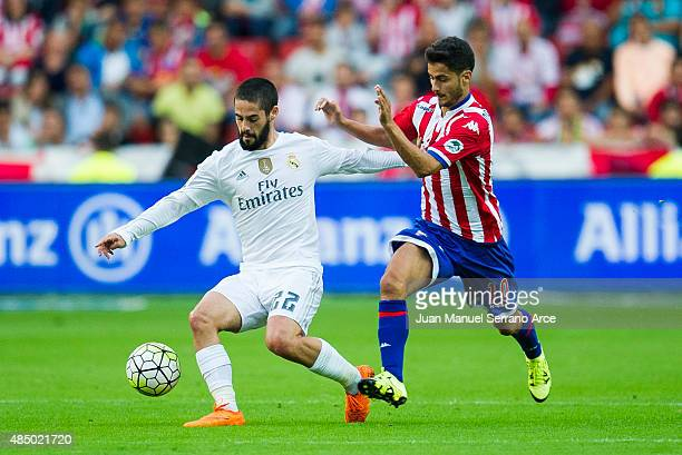 Isco of Real Madrid duels for the ball with Nacho Cases of Real Sporting de Gijon during the La Liga match between Sporting Gijon and Real Madrid at...