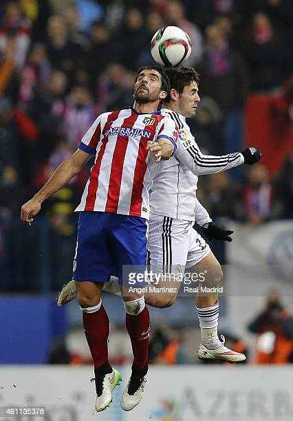 Isco of Real Madrid heads the ball against Raul Garcia of Atletico de Madrid during the Copa del Rey round of 16 first leg match between Club...