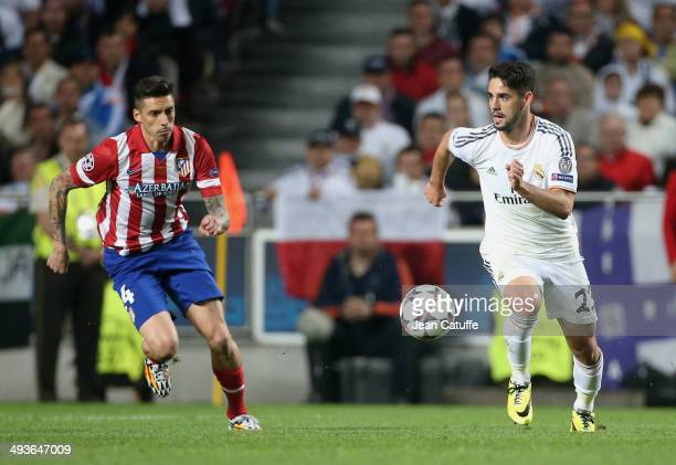 Isco of Real Madrid in action is watched by Jose Ernesto Sosa of Atletico Madrid during the UEFA Champions League final between Real Madrid and...