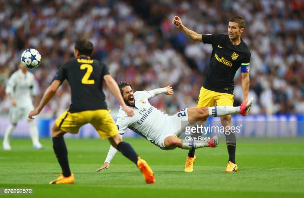 Isco of Real Madrid is challenged by Gabi and Diego Godin of Atletico Madrid during the UEFA Champions League semi final first leg match between Real...