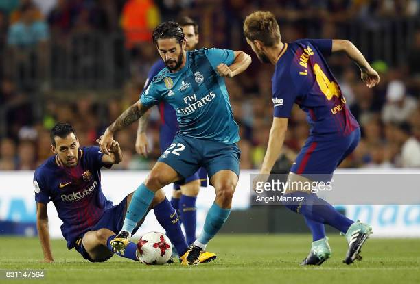 Isco of Real Madrid is challenged by Sergio Busquets and Ivan Rakitic of FC Barcelona during the Supercopa de Espana Final first leg match between FC...