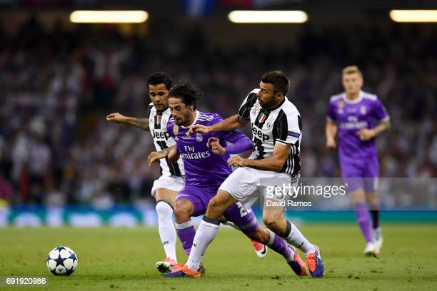 Isco of Real Madrid is fouled by Dani Alves of Juventus and Andrea Barzagli of Juventus during the UEFA Champions League Final between Juventus and...