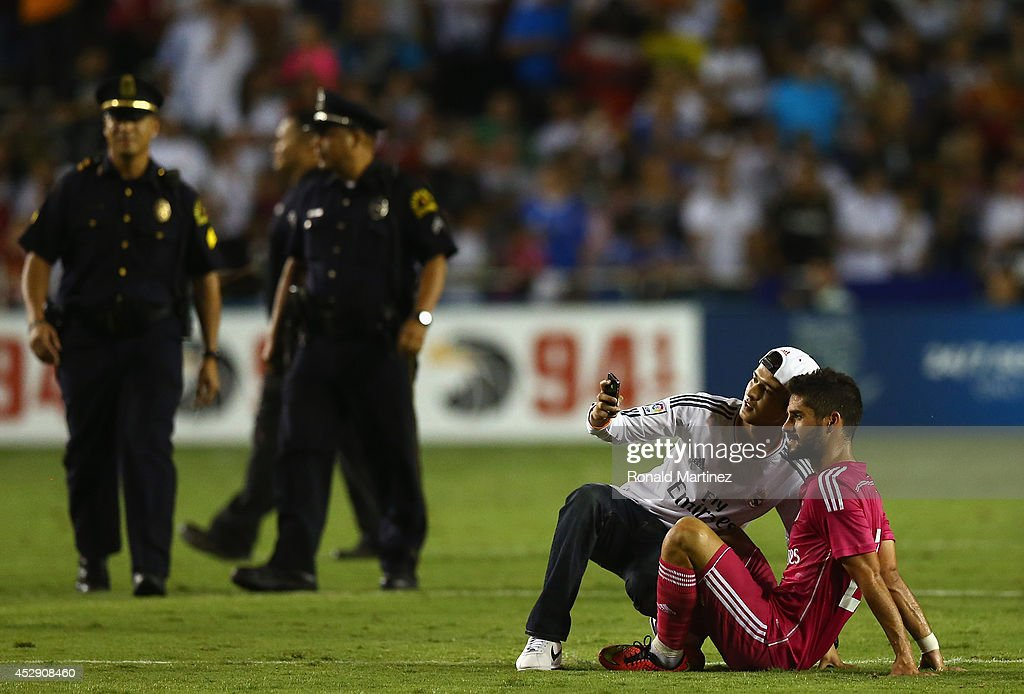 Isco #23 of Real Madrid takes a photo with a fan, after fans disrupted the game against AS Roma during a Guinness International Champions Cup 2014 game at Cotton Bowl on July 29, 2014 in Dallas, Texas.