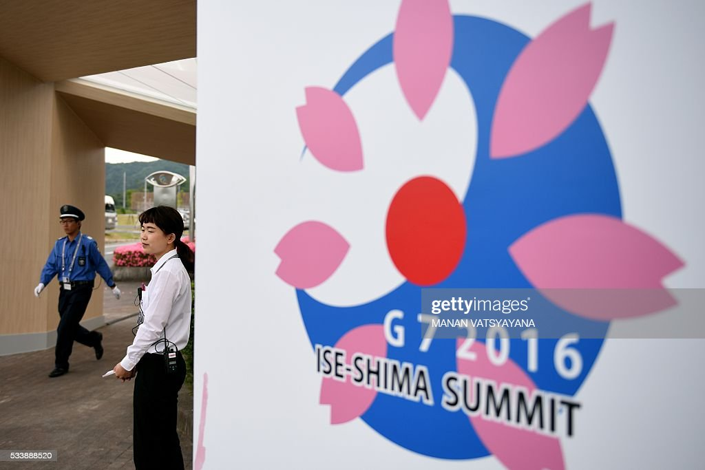 Ise-Shima G7 Summit volunteer stands next to the summit's logo at the International Media Center in Ise-Shima, 300 kilometres southwest of Tokyo on May 24, 2016. The lacklustre global economy should take centre stage as world leaders gather in Japan this week, but with no agreement likely on igniting growth, Barack Obamas visit to the atomic-bombed city of Hiroshima looks set to capture the limelight. / AFP / MANAN