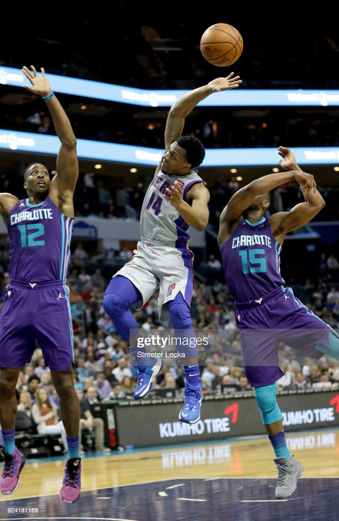 Ish Smith #14 of the Detroit Pistons drives to the basket against Teammates Dwight Howard #12 and Kemba Walker #15 of the Charlotte Hornets during their game at Spectrum Center on February 25, 2018 in Charlotte, North Carolina.