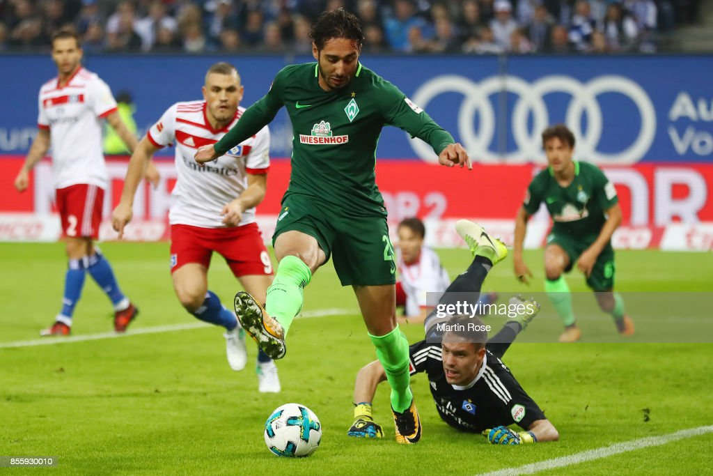 Ishak Belfodil of Bremen (front) fights for the ball with goalkeeper Christian Mathenia of Hamburg during the Bundesliga match between Hamburger SV and SV Werder Bremen at Volksparkstadion on September 30, 2017 in Hamburg, Germany.