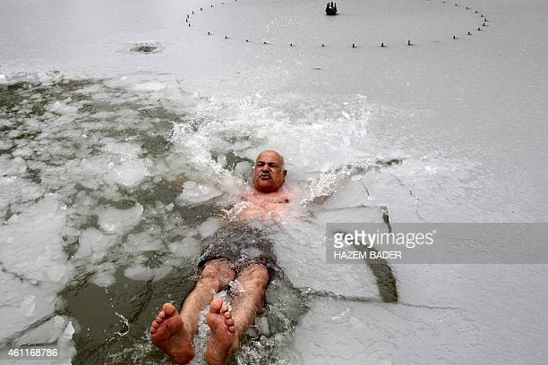 Ishaq Abu Romeileh a 65years old Palestinian man swims in a pond covered in ice in the city center of the West Bank town of Hebron on January 8 2015...