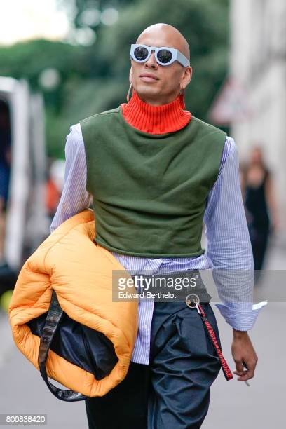 Ishmael Jeffers wears a striped shirt a green pull over with an orange collar pants and boots outside the Kenzo show during Paris Fashion Week...