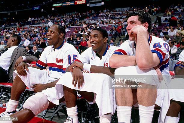 Isiah Thomas of the Detroit Pistons and his teammates watch from the sidelines during a 1989 NBA game at the Palace of Auburn Hills in Detroit...