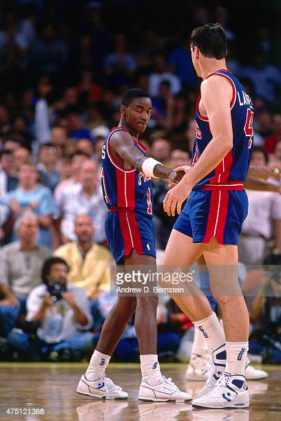 Isiah Thomas of the Detroit Pistons shakes hands with Bill Laimbeer against the Los Angeles Lakers during Game Six of the 1988 WNBA Finals on June 19...