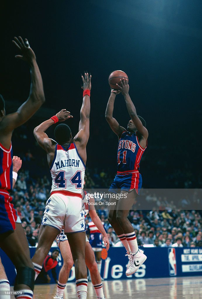Isiah Thomas of the Detroit Pistons shoots over Rick Mahorn of Washington Bullets during an NBA basketball game circa 1984 at The Capital Centre in...