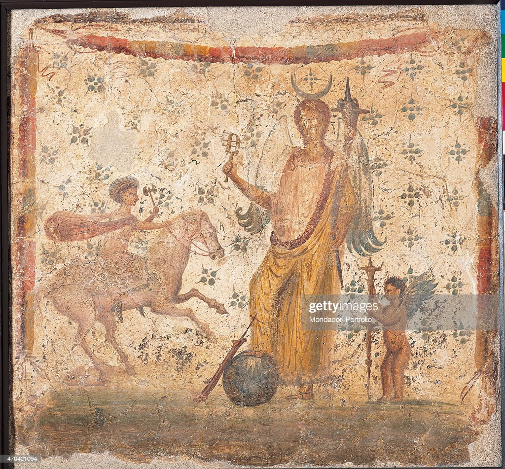 'Isis Fortuna, by unknown artist, 62-79, 1st Century A.D., ripped fresco, 37 x 24 cm Italy, Campania, Naples, National Archaeological Museum, Room LXXV, inv. 8836. Whole artwork view. On a white background decorated with star-shaped motifs, goddess Isis Fortuna, a waxing moon on her head, a musical instrument named sistrus in her right hand, a horn of plenty and a helm, that lies under her foot beside a globe; on the right, a cupid with coloured wings brings a long torch; on the left, Harpocrates, depicted as a warrior, gallops towards the goddess, a crown around his head and a spear in his hand. (Photo by Luigi Spina/Electa/Mondadori Portfolio)',Italy, Campania, Naples, National Archaeological Museum, Room LXXV, inv. 8836. Whole artwork view. On a white background decorated with star-shaped motifs, goddess Isis Fortuna, a waxing moon on her head, a musical instrument named sistrus in her right hand, a horn of plenty and a helm, that lies under her foot beside a globe; on the right, a cupid with coloured wings brings a long torch; on the left, Harpocrates, depicted as a warrior, gallops towards the goddess, a crown around his head and a spear in his hand.